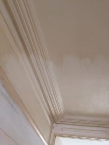 Ceiling with nicotine stains being cleaned before painting