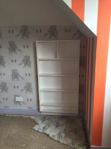 Remodelling project showing new wallpaper, painting and shelves which double as a hidden door to play room